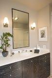 Lámparas por el espejo sobre el lavabo en cuarto de baño Fotos de archivo