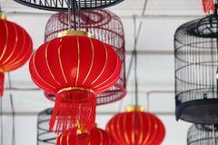 Lámparas rojas de la tela y lámparas de la jaula de pájaros que cuelgan en el techo Imágenes de archivo libres de regalías