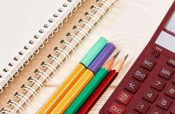 L?pices, calculadora de escritorio y cuadernos coloreados en la tabla de madera blanca Fuentes de la escuela y de oficina Visi?n  fotos de archivo