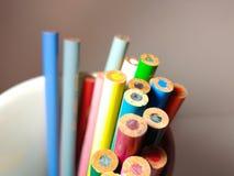 Lápices coloreados afilados que se pegan fuera de una taza al revés fotografía de archivo libre de regalías