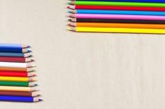 Lápices coloreados brillantes en el fondo de papel Foto de archivo libre de regalías