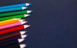 Lápices coloreados contra fondo azul marino Foco ascendente y selectivo del cierre fotografía de archivo libre de regalías