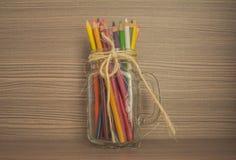 Lápices coloreados dentro de la taza de cristal imágenes de archivo libres de regalías
