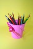 Lápices coloreados en cubo rosado Imagen de archivo libre de regalías