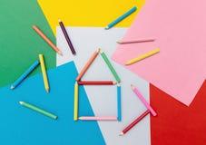 Lápices coloreados en la forma de una casa en el papel coloreado imagenes de archivo