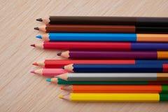 Lápices coloreados en un escritorio de madera de la escuela Fotos de archivo