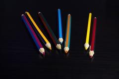 Lápices coloreados en un fondo de madera oscuro Fotografía de archivo