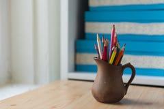 Lápices coloreados en un jarro hermoso imagenes de archivo