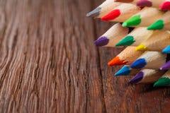 Lápices coloreados en un tablero de madera Fotografía de archivo