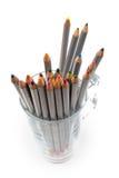 Lápices coloreados en una taza de cristal Imágenes de archivo libres de regalías