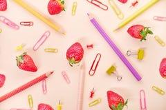 Lápices coloreados, fuentes de escuela, fresa Fondo del resorte imagen de archivo