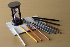 Lápices coloreados, notas y un temporizador Foto de archivo libre de regalías