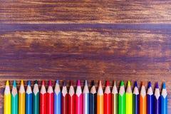 Lápices coloreados puestos en endecha del plano de la fila fotografía de archivo