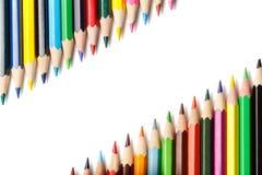 Lápices coloreados que mienten en esquinas opuestas Foto de archivo libre de regalías