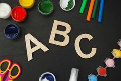 Lápices coloridos cortados laser de la pizarra de madera de la pizarra de las letras de ABC de las fuentes de escuela, pintura, t Imágenes de archivo libres de regalías