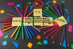 Lápices coloridos en círculos, títulos de nuevo a escuela y el autobús escolar dibujado en los trozos de papel en la pizarra Fotos de archivo