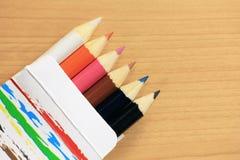 Lápices coloridos en la caja de papel Imágenes de archivo libres de regalías