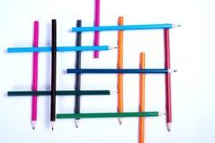 Lápices coloridos organizados en una forma geométrica en el backgrou blanco Imagen de archivo libre de regalías