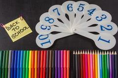 Lápices coloridos, tarjetas de números y título de nuevo a la escuela escrita en el trozo de papel en la pizarra Foto de archivo libre de regalías