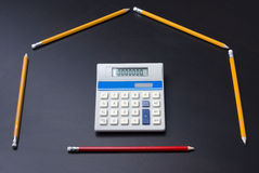 Lápices como casa con la puerta de la calculadora Imagen de archivo libre de regalías