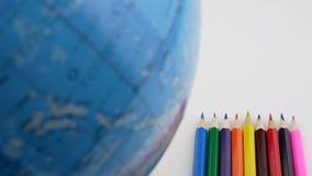 L?pices de madera coloridos y globo giratorio De nuevo al concepto de la escuela Espacio en blanco para la muestra metrajes