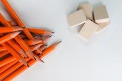 Lápices de madera simples de Gaphite en la tabla aislada con los borradores fotografía de archivo libre de regalías