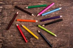 Lápices del color dispersados en el fondo de madera Imagenes de archivo