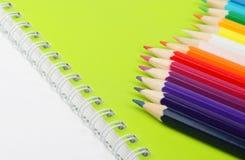 Lápices del color en el cuaderno verde Imágenes de archivo libres de regalías