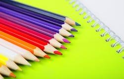 Lápices del color en el cuaderno verde Imagen de archivo
