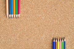 Lápices del color en fondo del tablero del corcho Foto de archivo libre de regalías