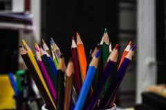 Lápices del color en fondo del negro de sitio del artista foto de archivo libre de regalías