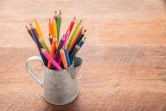 Lápices del color en la lata, fondo de madera de la tabla Concepto de la educación foto de archivo libre de regalías