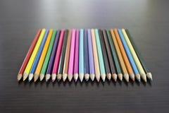 Lápices del color en la tabla en fila Imagen de archivo libre de regalías