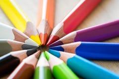 Lápices del color en la textura de madera Imagen de archivo