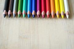Lápices del color en la textura de madera Fotografía de archivo