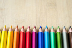 Lápices del color en la textura de madera Foto de archivo