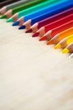 Lápices del color en la textura de madera Imagenes de archivo