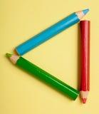 Lápices del color que forman un marco del triángulo Foto de archivo libre de regalías