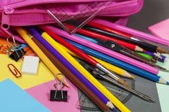 Lápices del colorante que desbordan una caja de lápiz rosada Imagenes de archivo