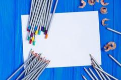 Lápices en blanco del trozo de papel y del color en backgrou de madera rústico Imagenes de archivo