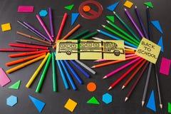 Lápices en círculos, títulos de nuevo a escuela y el dibujo del autobús escolar dibujado en los trozos de papel en la pizarra Foto de archivo