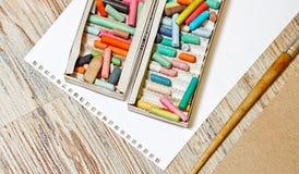 Lápices en colores pastel del equipo en la caja Imagenes de archivo