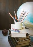 Lápices en taza en la pila de libros y de globo, de nuevo todavía de la escuela a vida Foto de archivo libre de regalías