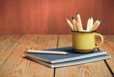 Lápices en una taza en una tabla de madera Foto de archivo libre de regalías