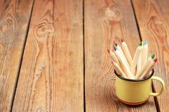 Lápices en una taza en una tabla de madera Fotos de archivo libres de regalías