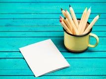 Lápices en una taza en una tabla de madera Fotografía de archivo libre de regalías