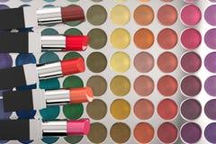 Lápices labiales en la paleta de la sombra de ojos ilustración del vector