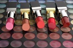 Lápices labiales en la paleta de la sombra de ojos stock de ilustración