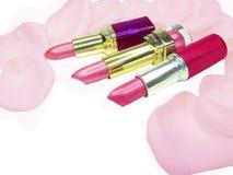 Lápices labiales rosados entre los pétalos color de rosa Fotos de archivo