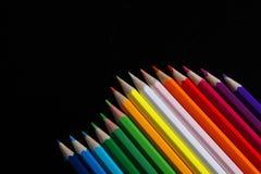 Lápices multicolores en fondo negro del espejo Fotos de archivo libres de regalías